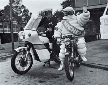 South Yorkshire Police: Constable David Burgum, Force motor cycle instructor, with 'friend' (Michelin Man) at the Roadcraft/Road Safety display - BIKEX '77