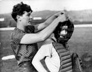 Member of the Sheffield Ladies Baseball Team assisting the 'Catcher' with her face guard
