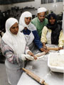 Group of women making chapattis at the Pakistan Muslim Centre, Woodbourn Road