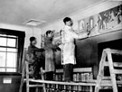 Three artists from the College of Arts painting the frieze at Hillsborough Junior Library, Hillsborough Library, Middlewood Road, Hillsborough Park. Formerly Hillsborough Hall and built in the 18th century.